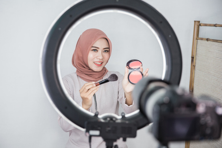 beauty blogger. makeup tutorial. video blog concept. portrait of asian muslim woman showing makeup tutorial online using camera and lighting equipment