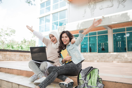portrait of two asian female college student using laptop on campus