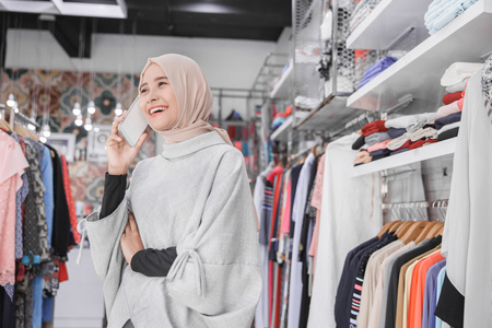 Beautiful asian muslim young woman using her smart phone with smile while standing at the clothing store 版權商用圖片