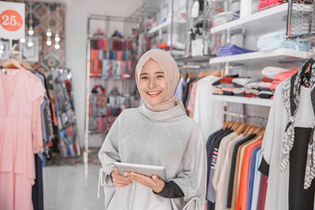 Retrato, de, um, jovem, muçulmano, executiva, com, bonito, sorrizo, segurando, tablete digital, enquanto, ficar, em, dela, moda, boutique, proprietário feminino