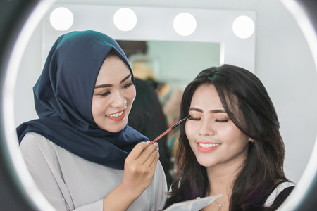 beautiful Make-up artist applying cosmetic with a brush on woman eyelids