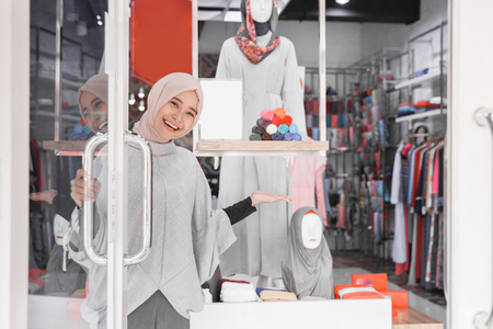 attractive muslim asian female worker welcoming customer to her boutique fashion store
