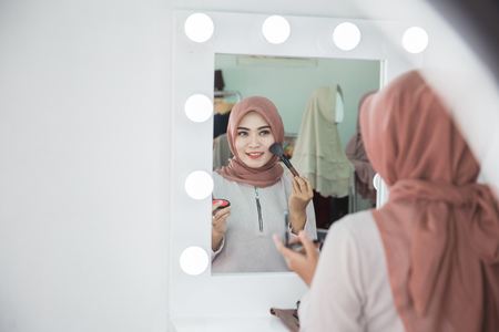 Beauty muslim woman with hijab applying makeup. Beautiful girl looking in the mirror and applying cosmetic. Girl gets blush on the cheekbones Archivio Fotografico