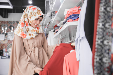 Beautiful excited muslim female with head scarf looking at blouse in fashion store 스톡 콘텐츠