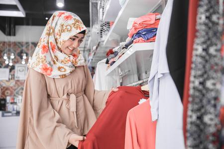 패션 가게에서 블라우스를보고있는 머리 스카프로 아름답고 흥분된 이슬람 여성