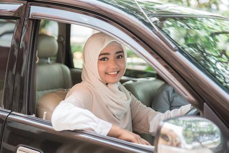 Porträt der muslimischen asiatischen jungen Frau , die ihr Auto fährt Standard-Bild - 92565795