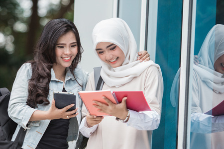 two university students studying together outside her campus