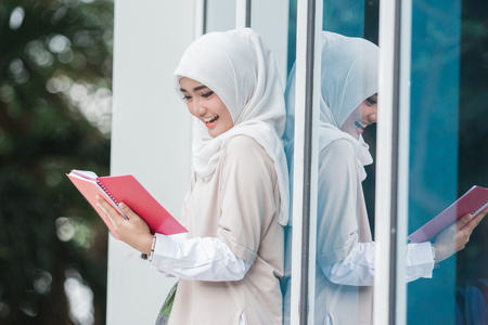 candid portrait of young asian muslim student on campus