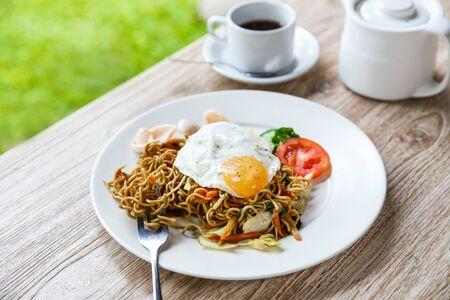 portrait of homemade indonesian fried noodle with a cup of hot tea for breakfast