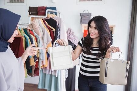 ファッションブティックオーナー若いアジアの女性は、彼女の女性のクライアントが購入するために2つの手の財布を保持