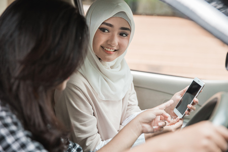 portrait of young woman showing her mobile phone to friend while driving a car. Giving direction via GPS Фото со стока - 92565831