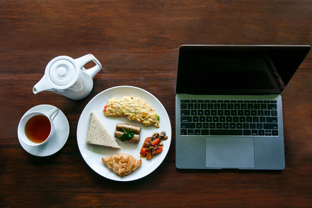 top view portrait of english breakfast with a cup of a tea and a laptop on the table Stock Photo