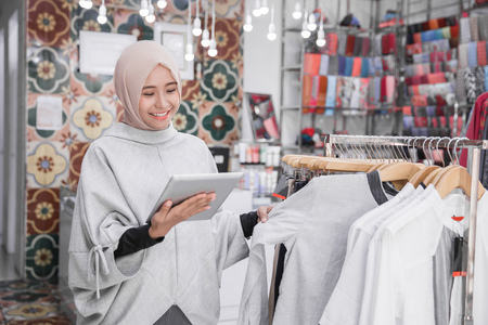 Portrait of a young muslim businesswoman with beautiful smile holding digital tablet checking stock in her fashion boutique, female owner Banque d'images
