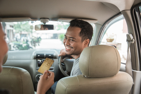 customer paying for taxi. cashless payment in commercial transportation Stok Fotoğraf