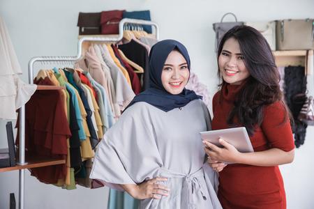 portret van mode winkeleigenaar en haar assistent met behulp van tablet in mode winkel Stockfoto