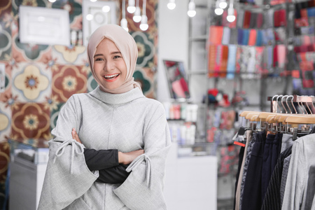 portrait of attractive asian female business owner standing crossed arm in her boutique fashion store. muslim entrepreneur concept