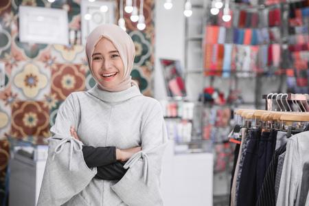 retrato do empresário feminino asiático atraente em pé cruzou o braço em sua loja de moda boutique. conceito de empresário muçulmano Foto de archivo