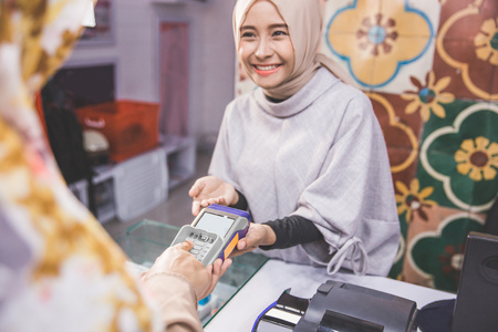customer put her secret number while pay using credit card at fashion store