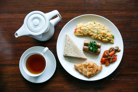 top view portrait of english breakfast with a cup of a tea on wooden table