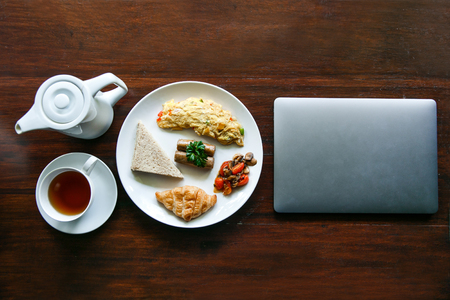 top view portrait of english breakfast with a cup of a tea and a laptop on wooden table