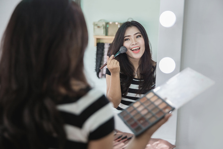 Beauty woman applying makeup. Beautiful girl looking in the mirror and applying cosmetic. Girl gets blush on the cheekbones Stock fotó