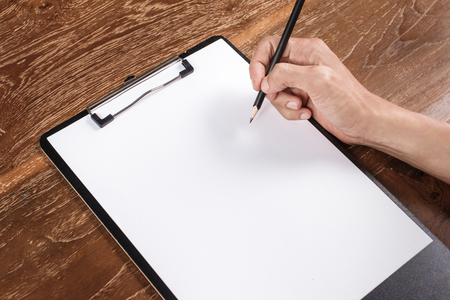 hand holding pencil and blank letterhead for corporate identity