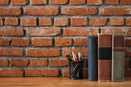 books and stationary supplies on wooden table with brick wall ba