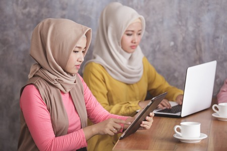two woman wearing hijab are busy on their own gadget