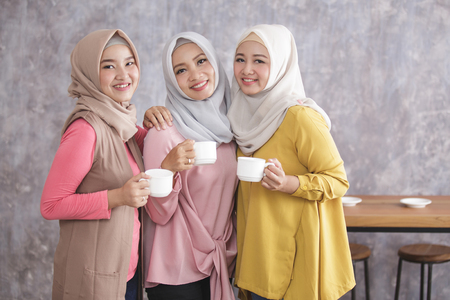 three beautiful muslim woman standing and smiling while holding