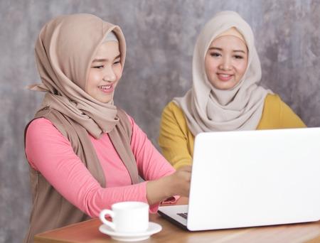 beautiful muslim women presenting something on laptop to her sib