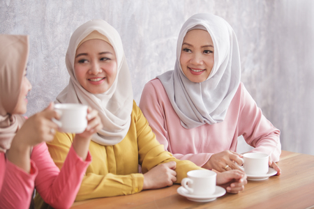 three beautiful siblings having an a coffee time together Stock Photo