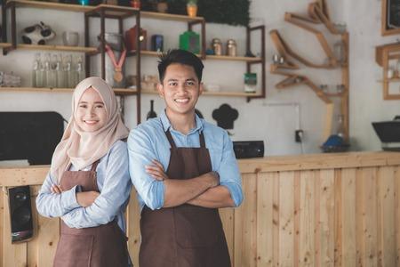 twee café-eigenaar staan met gekruiste armen Stockfoto