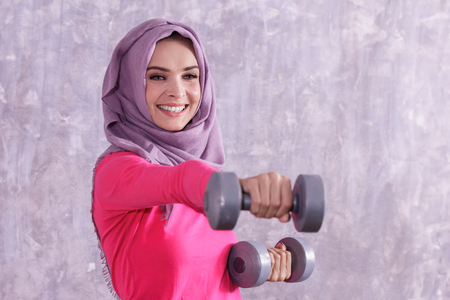 beautiful hijab sporty woman workout using dumbbell