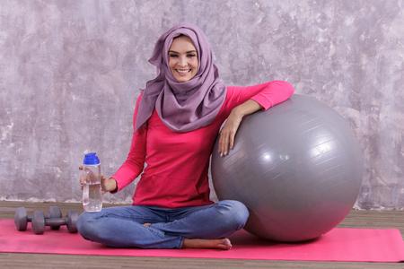 beautiful healthy woman wearing hijab siting on yoga mat