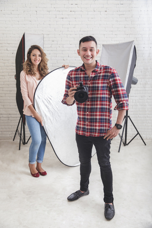 young photographer with his beautiful assistant in studio Stock Photo