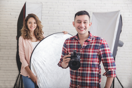 young photographer with his beautiful assistant in studio Stok Fotoğraf