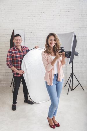 jonge mooie fotograaf met haar assistent in de studio klaar