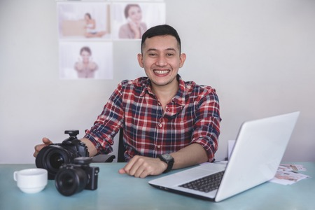young photographer sitting on his office with his print photo re
