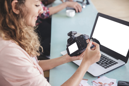 young female photographer inserting the memory card to the camer