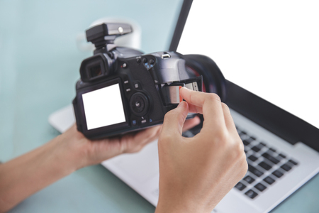 hand of photographer inserting the memory card to the camera Stock Photo - 92218059