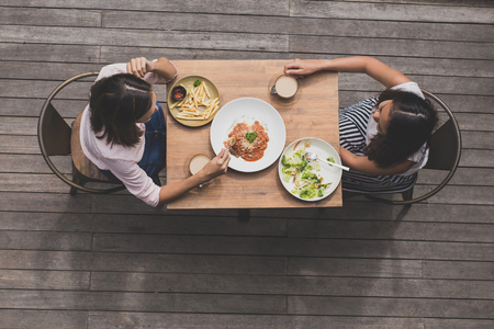 two young woman having lunch together