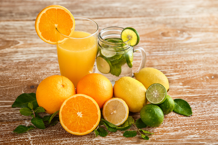 portrait of fresh orange juice and classic mojito with orange, lime, and mint around on wooden background Stock Photo