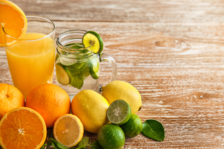 portrait of fresh orange juice and classic mojito with orange, lime, and mint around on wooden background with copy space