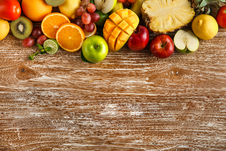 portrait of fresh mixed fruits on rustic wooden background with copy space