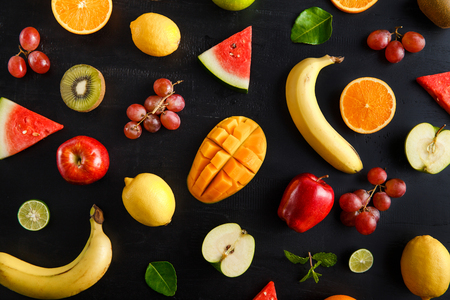 top view portrait of fresh mixed tropical fruits pattern on black background Imagens