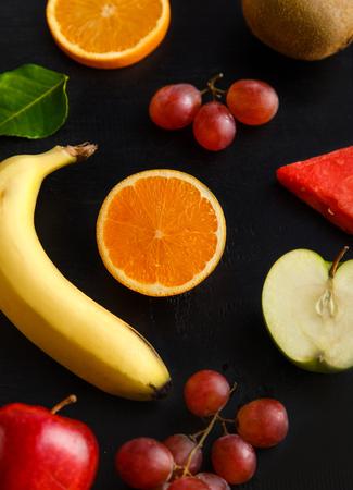 검은 색 바탕에 신선한 혼합 열대 과일의 초상화
