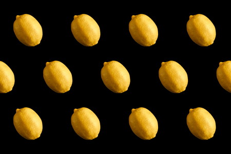 top view portrait of fruit pattern of fresh yellow lemon on black background Stock Photo