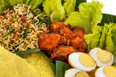 portrait of spicy chicken on nasi tumpeng, indonesian cuisine