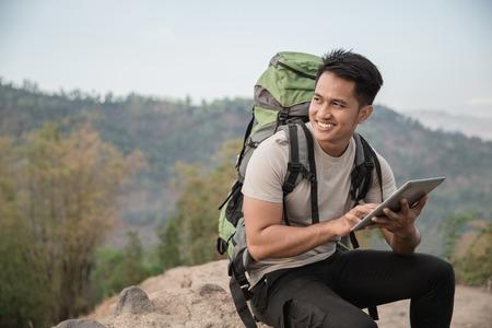 turysta mężczyzna przy użyciu komputera typu tablet. podziwiając widok na las