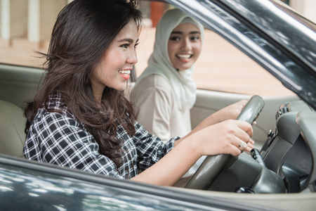 Two young women hangout on car trip.They are driving the car together